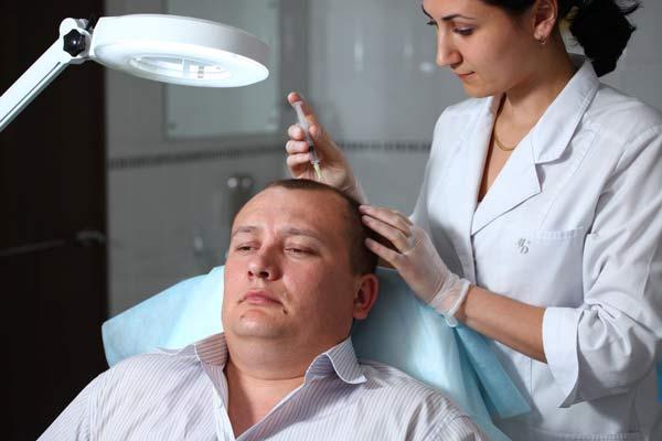 Лысого мужчину обследует доктор